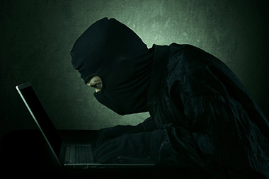 Hacker typing on a laptop and looking at computer screen